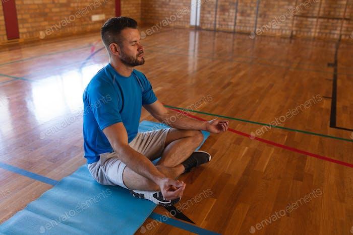 Yogalehrer macht Yoga und meditiert auf einer Yogamatte in der Schule
