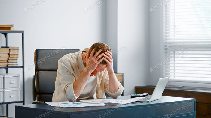 Upset financial director reads bank reports sitting at grey table