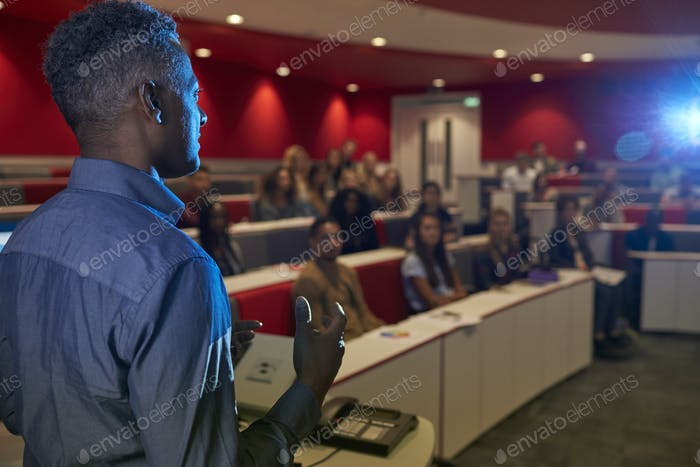 Man lecturing students in a university lecture theatre
