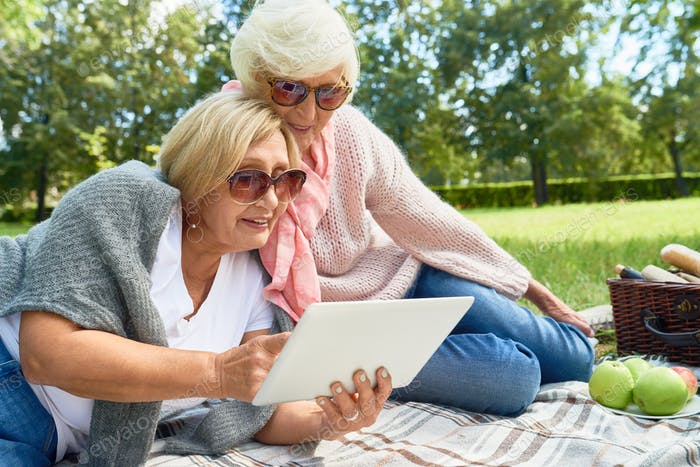 Two Senior Women Using  Tablet in Park