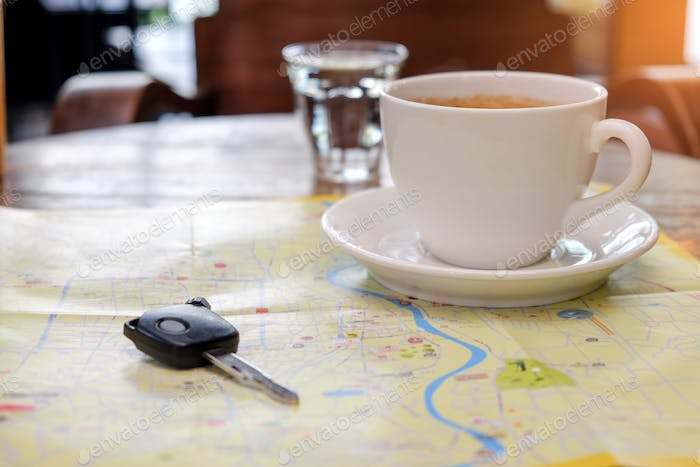 Coffee and car key place on the map with glass water.