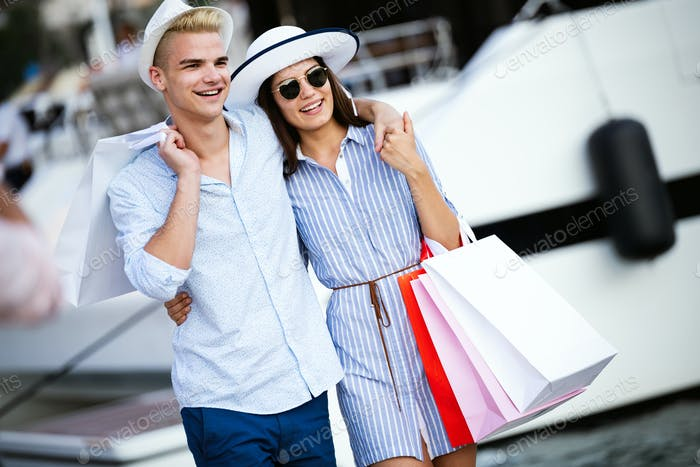 People,sale,love and happiness concept. Portrait of a couple with shopping bags in the city