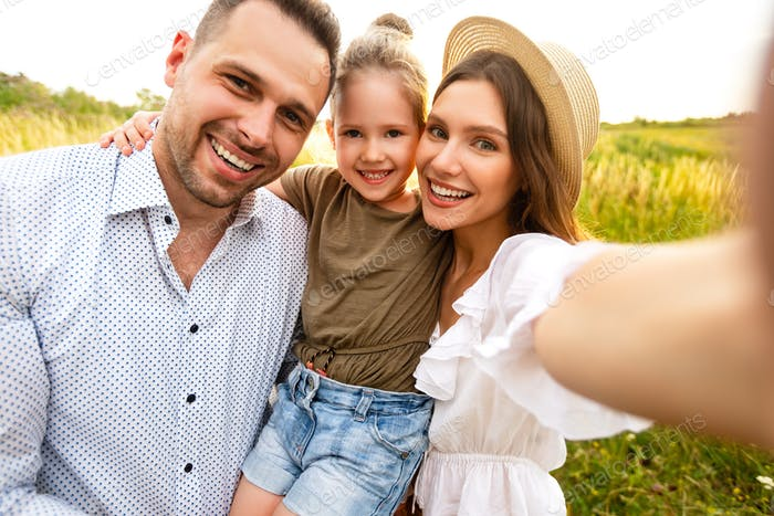 Happy loving family taking selfie on a picnic outdoor