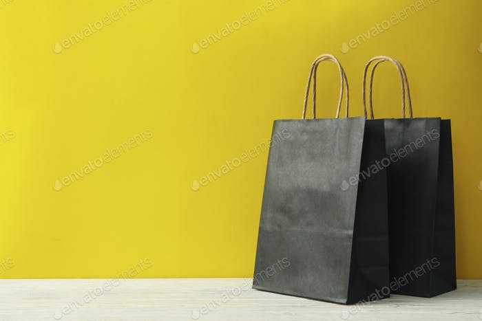 Paper bags on wooden table against yellow background