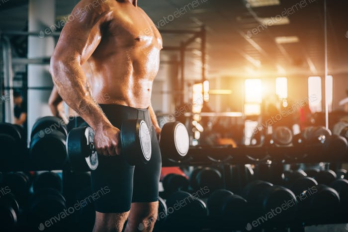 Muscular man holding dumbbels in a gym.