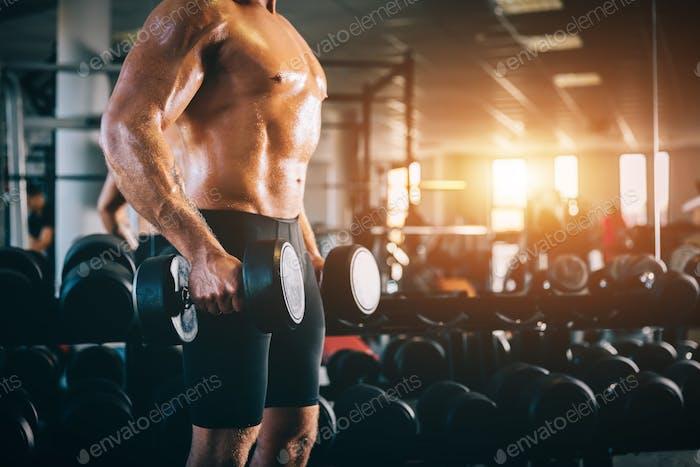 Muskulöser Mann hält Hanteln in einem Fitnessstudio.