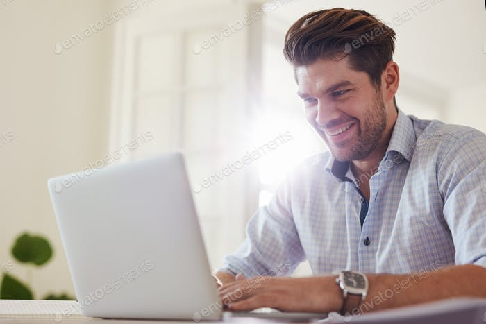 Happy businessman working from home office