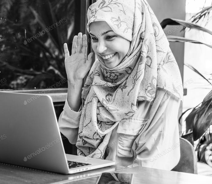 Islamic woman using laptop foe video call with happy face