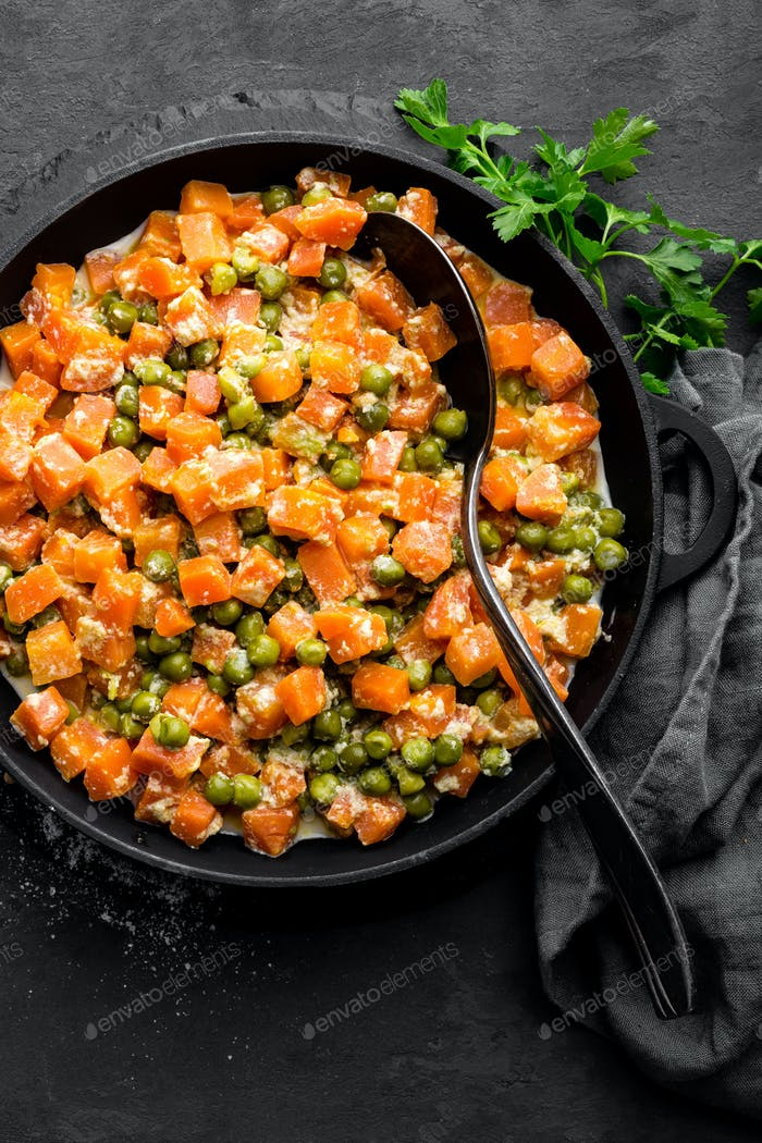 Carrot braised with fresh green peas in creamy milk sauce in stewpan, vegetable saute
