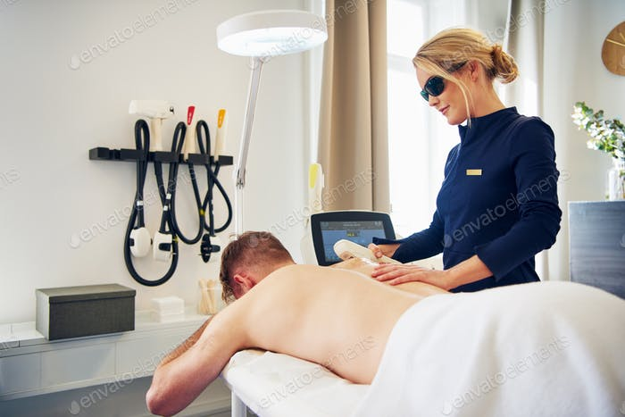 Beautician performing laser hair removal on a male client