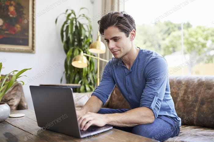 молодой кавказский человек используя ноутбук в кафе