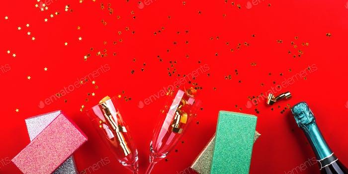 Champagner, Geschenke und Flöte auf rot mit Konfetti