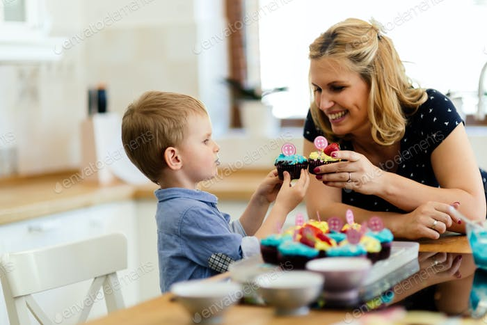 Mother and child joyfully eating muffins