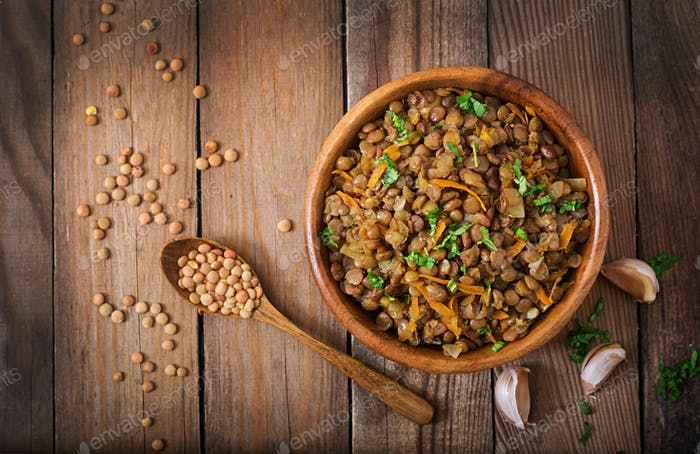 Lentil with carrot and onion in wooden bowl. Healthy lifestyle. Diet menu. Flat lay. Top view