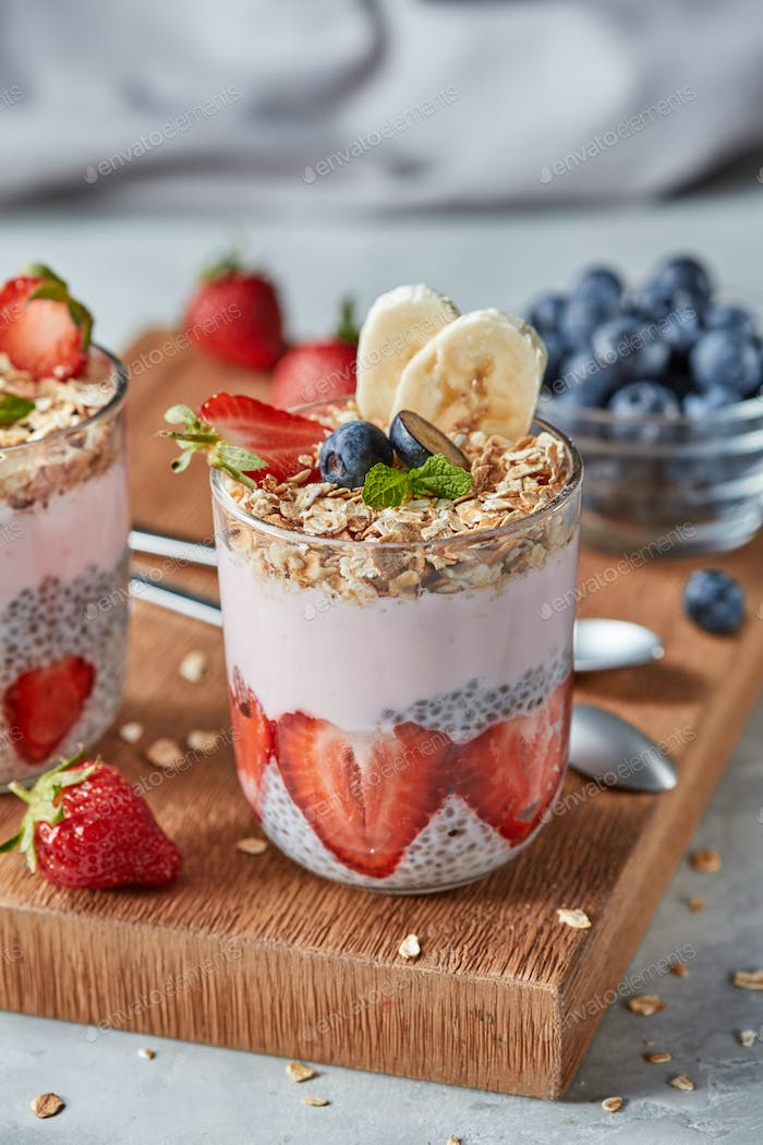 Dietary natural breakfast with fresh organic ingredients - berries, granola, banana in a glass on a