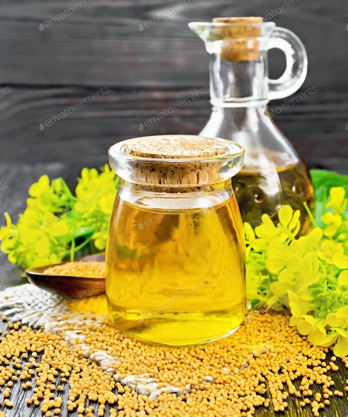 Oil mustard in jar and decanter with flower on burlap
