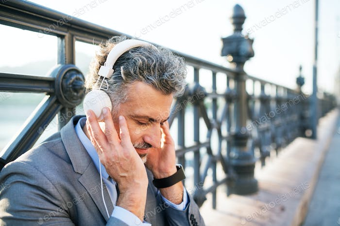 Mature businessman with headphones in a city.