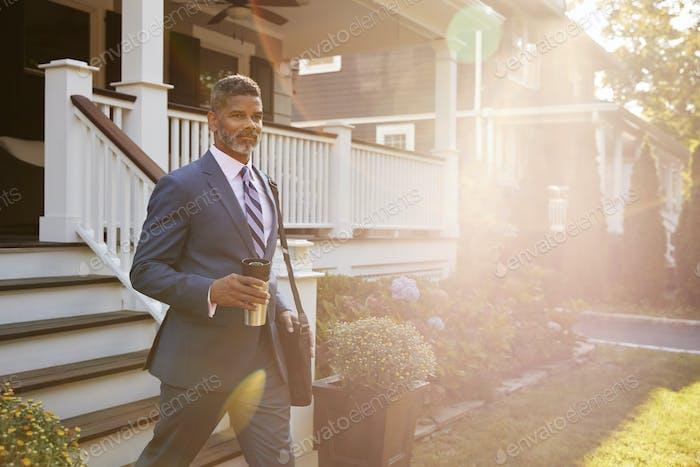 Geschäftsmann mit Tasse Kaffee verlassen Suburban Haus für die Arbeit