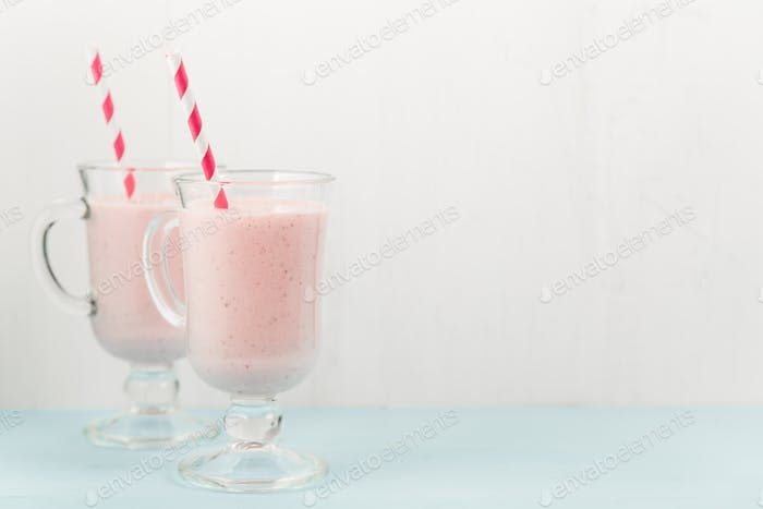 Two ice-cream pink cocktails with strawberries
