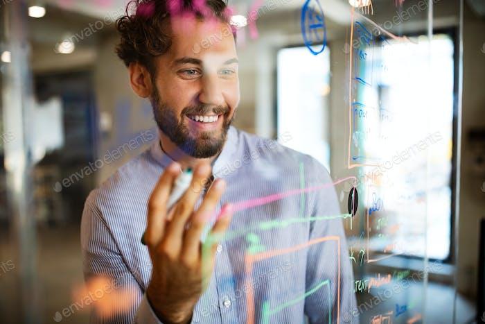 Junger Mann, der mit Daten und Diagrammen arbeitet, Ideen auf Glas Bürowand schreiben