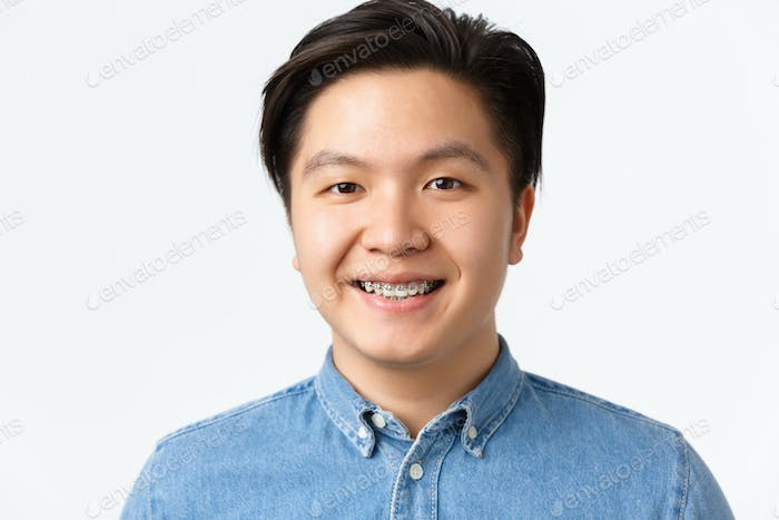 Orthodontics, dental care and stomatology concept. Close-up portrait of handsome asian man with