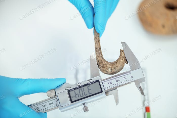 Archaeologist Measuring Ancient Hook with Digital Caliper