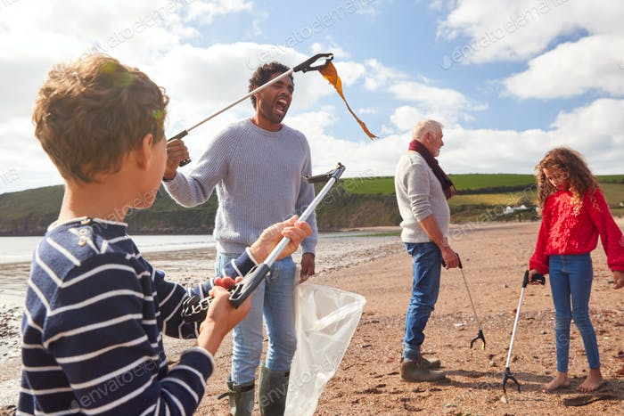 Multi-Generation Family Collecting Litter On Winter Beach Clean Up