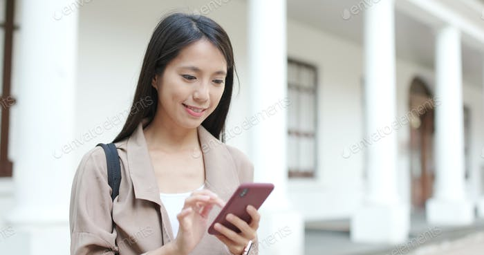 Woman sending text message on cellphone at outdoor
