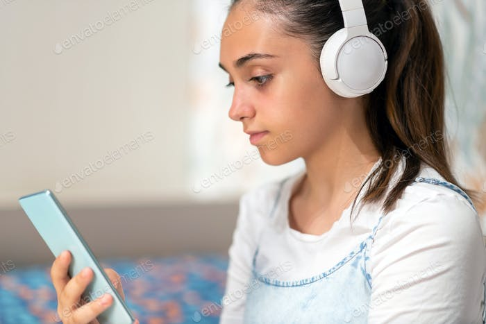Absorbed young teenage girl listening to music on her mobile