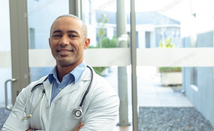 Front view of Mixed-race male doctor with arm crossed looking at camera in hospital