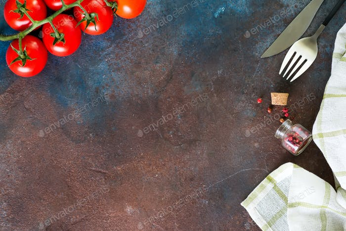 napkin, cutlery and cherry tomatoes on dark stone background, top view, copy space