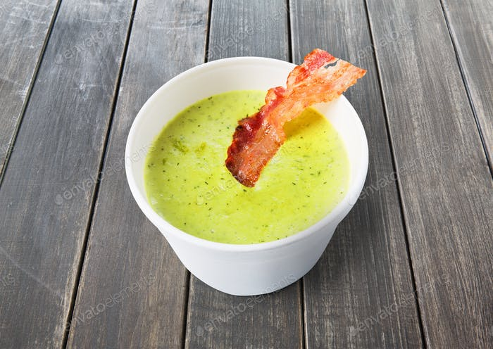 Green spring pea soup with bacon at gray wood