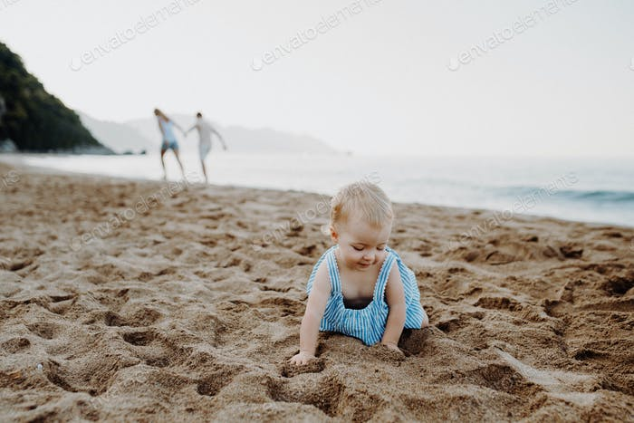 A small toddler girl playing in sand on beach on summer holiday.