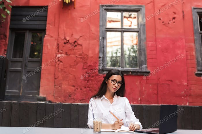 Beautiful girl with dark hair in white shirt and eyeglasses drea