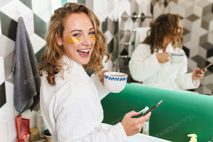 Image of young woman with eye patches holding cellphone and coffee cup
