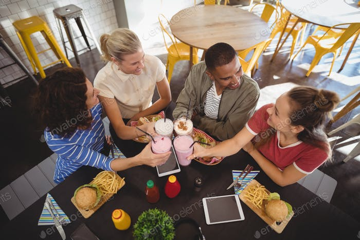 High angle view of smiling young friends raising toast while sitting at coffee shop
