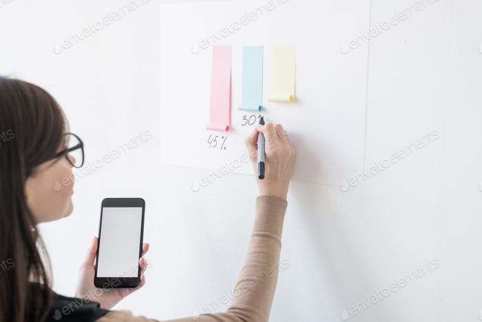 Young female broker writing down percentage under paper chart on whiteboard