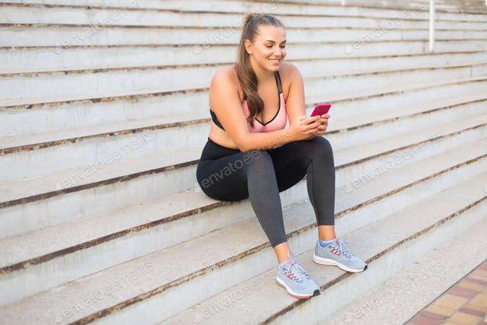 Young cheerful plus size woman in sporty top and leggings sittin