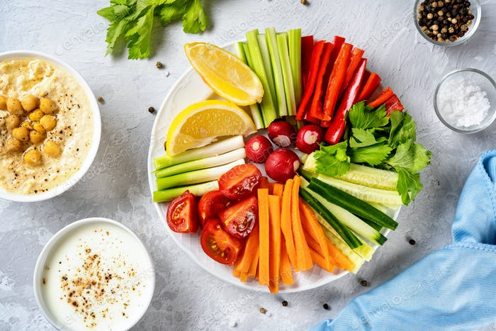 Close up of a plate with cut vegetables and dips