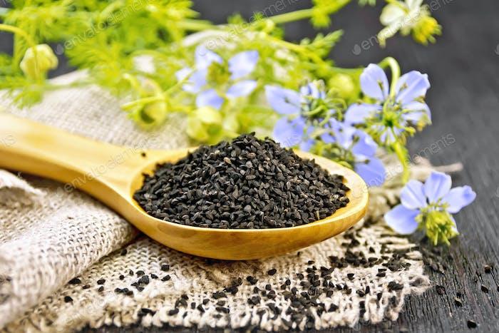 Seeds of black cumin in spoon on board