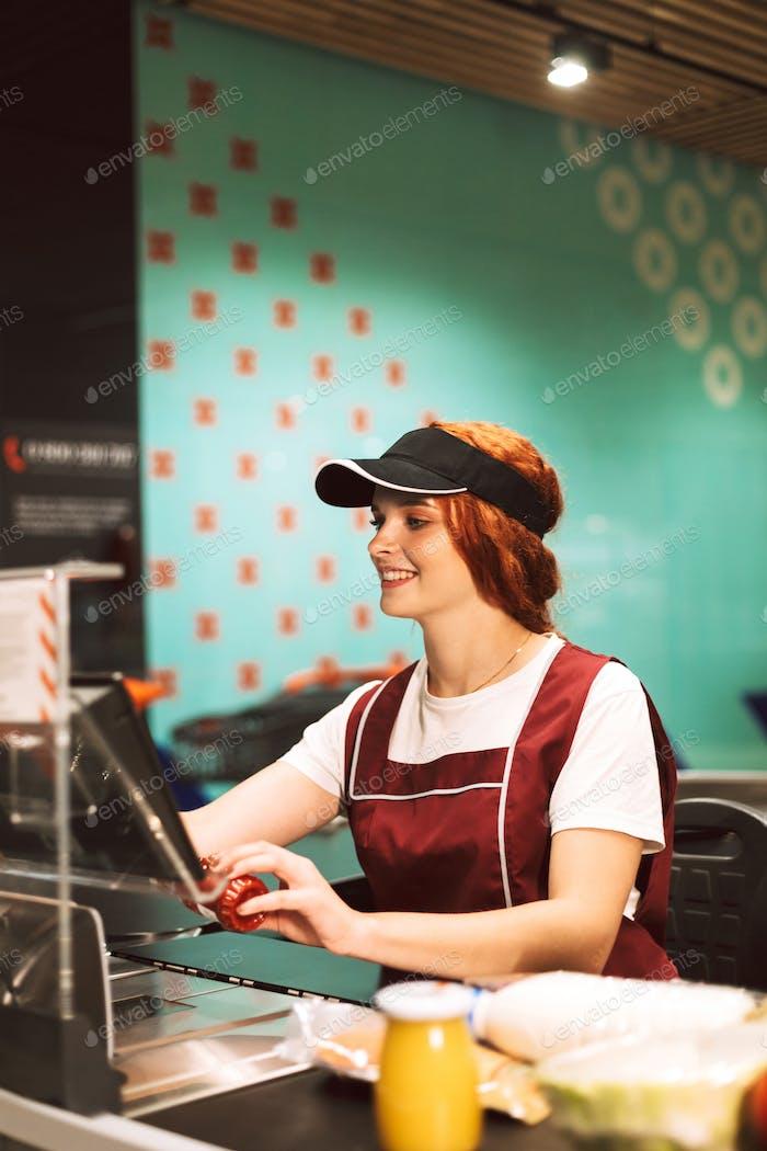 Young smiling female cashier in uniform joyfully using cashbox w