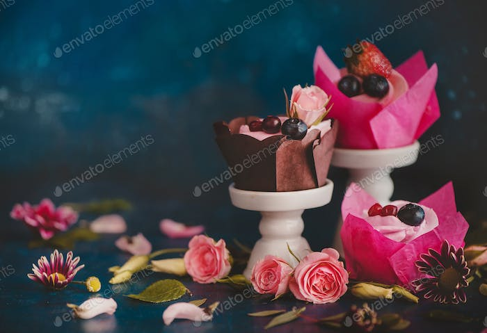 Cupcakes with on porcelain stands with rose flowers on a dark background. Spring dessert concept