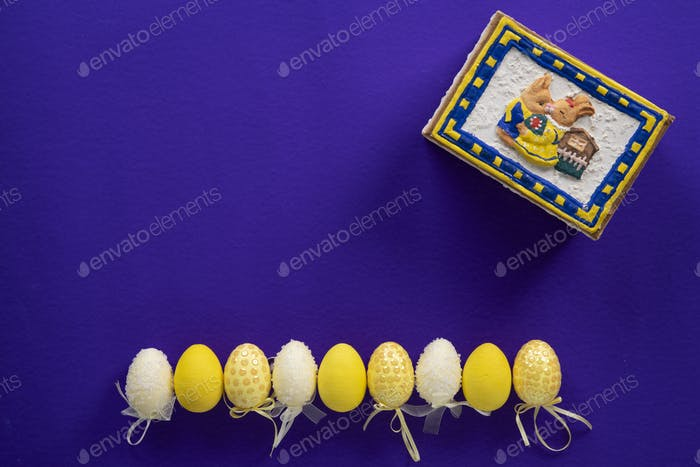 White and yellow fake plastic easter eggs and a closed bunny box