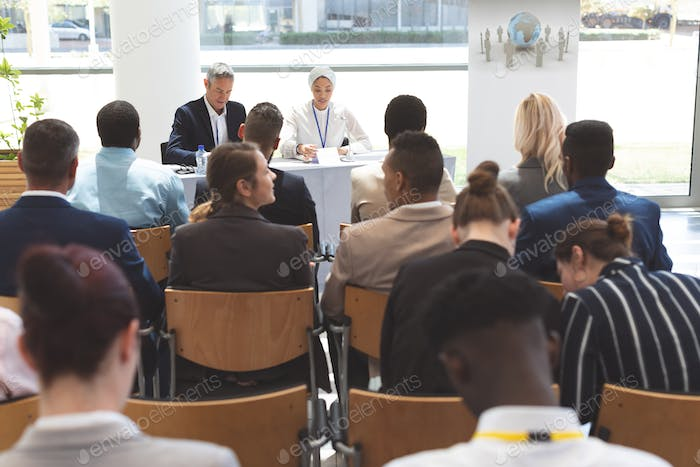 Rear view of diverse group of business people attending a business seminar in office building