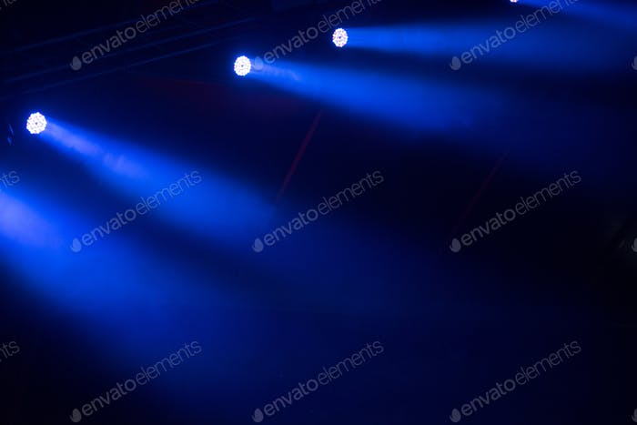 Glowing blue stage lights in the dark
