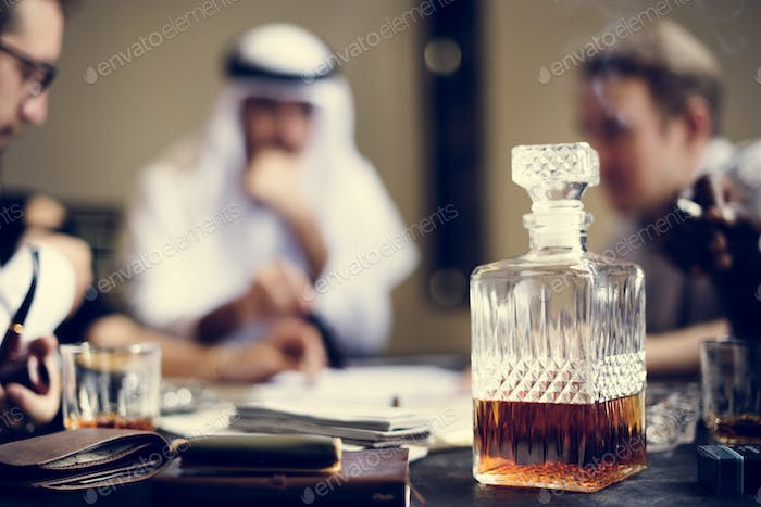 Whiskey decanter with business people in the background