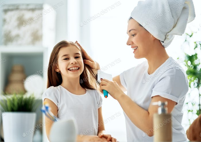Mother and daughter combing hair