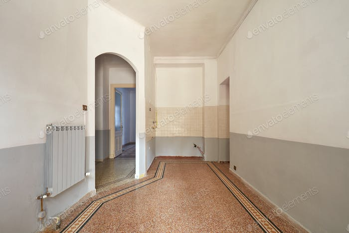 Empty living room and kitchen area interior with tiled floor