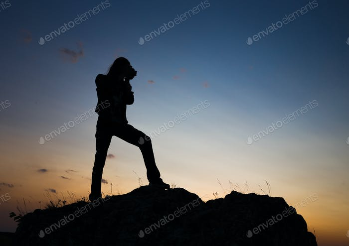 Silhouette of longhair male model with camera.