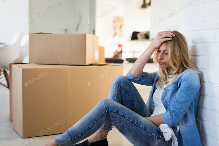 Müde Frau erschöpft beim Umzug in neues Zuhause